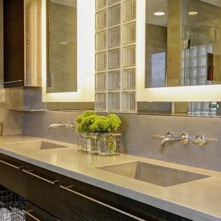 Idee per un'ampia stanza da bagno padronale minimalista con lavabo integrato, ante lisce, ante nere, top in cemento, doccia alcova, piastrelle grigie, piastrelle in gres porcellanato e pavimento in gres porcellanato