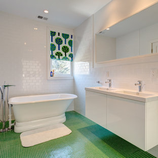 Example of a large minimalist kids' white tile and subway tile green floor and ceramic floor bathroom design in New York with flat-panel cabinets, a two-piece toilet, white walls, an integrated sink, solid surface countertops, white cabinets and white countertops