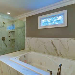 Modelo de cuarto de baño infantil, clásico renovado, de tamaño medio, con lavabo bajoencimera, armarios con paneles con relieve, puertas de armario de madera clara, encimera de cuarcita, jacuzzi, ducha abierta, sanitario de una pieza, baldosas y/o azulejos grises, baldosas y/o azulejos de porcelana, paredes beige y suelo de baldosas de porcelana