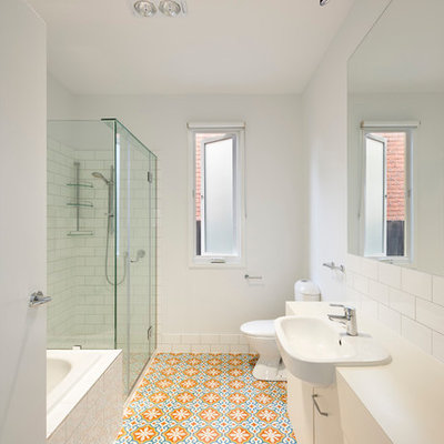 Inspiration for a mid-sized contemporary white tile and subway tile ceramic tile and multicolored floor bathroom remodel in Melbourne with flat-panel cabinets, white cabinets, a one-piece toilet, white walls, a drop-in sink, laminate countertops, a hinged shower door and white countertops