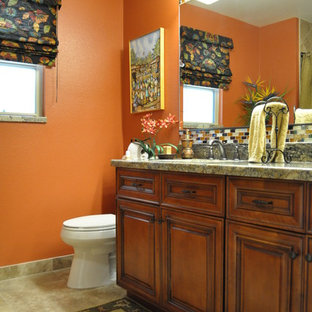Diseño de cuarto de baño rural con lavabo bajoencimera, puertas de armario de madera oscura, encimera de granito, sanitario de una pieza, baldosas y/o azulejos multicolor, baldosas y/o azulejos de vidrio laminado, parades naranjas y suelo de baldosas de porcelana