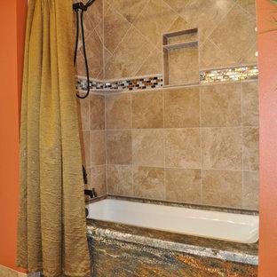 Immagine di una stanza da bagno con doccia rustica con lavabo sottopiano, ante con bugna sagomata, ante in legno scuro, top in granito, vasca da incasso, vasca/doccia, WC monopezzo, piastrelle beige, piastrelle di vetro, pareti arancioni e pavimento con piastrelle in ceramica