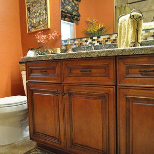 フェニックスの中サイズのラスティックスタイルのおしゃれなバスルーム (浴槽なし) (アンダーカウンター洗面器、レイズドパネル扉のキャビネット、中間色木目調キャビネット、御影石の洗面台、アルコーブ型シャワー、一体型トイレ、ベージュのタイル、ガラス板タイル、オレンジの壁、セラミックタイルの床) の写真