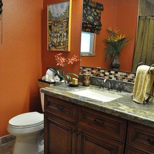 Foto de cuarto de baño con ducha, rústico, de tamaño medio, con lavabo bajoencimera, armarios con paneles con relieve, puertas de armario de madera oscura, encimera de granito, sanitario de una pieza, baldosas y/o azulejos multicolor, baldosas y/o azulejos de vidrio laminado, parades naranjas y suelo de baldosas de cerámica