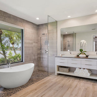 Example of a coastal master gray tile medium tone wood floor and brown floor bathroom design in Miami with flat-panel cabinets, white cabinets, gray walls, a drop-in sink and gray countertops