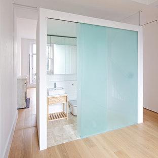 Modelo de cuarto de baño vestidor, minimalista, con lavabo sobreencimera, puertas de armario de madera clara, baldosas y/o azulejos blancos, baldosas y/o azulejos de cemento, paredes blancas, suelo de madera clara, sanitario de una pieza y armarios abiertos