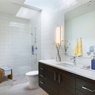 Trendy white tile gray floor bathroom photo in Minneapolis with flat-panel cabinets, dark wood cabinets, an undermount sink and white countertops