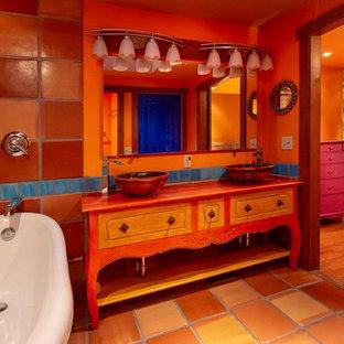 Ejemplo de cuarto de baño principal, de estilo americano, con armarios tipo mueble, puertas de armario naranjas, bañera con patas, ducha abierta, sanitario de una pieza, baldosas y/o azulejos naranja, baldosas y/o azulejos de terracota, parades naranjas, suelo de baldosas de terracota, lavabo sobreencimera, suelo naranja, ducha con cortina y encimeras naranjas