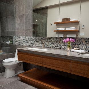 Immagine di una stanza da bagno contemporanea con top in pietra calcarea, lavabo sottopiano, ante in legno bruno e piastrelle di ciottoli