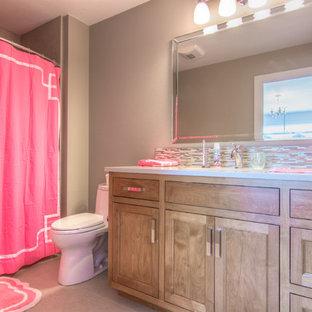 Immagine di una stanza da bagno chic con ante con riquadro incassato, ante in legno bruno, vasca da incasso, piastrelle in pietra, pareti grigie, lavabo sottopiano e top in granito