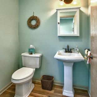Foto de cuarto de baño tradicional renovado, de tamaño medio, con lavabo con pedestal, armarios tipo vitrina, puertas de armario blancas, sanitario de dos piezas, paredes verdes y suelo de madera en tonos medios