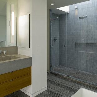 Imagen de cuarto de baño moderno con lavabo de seno grande, armarios con paneles lisos, puertas de armario de madera oscura, encimera de cemento, ducha empotrada, baldosas y/o azulejos grises y azulejos en listel