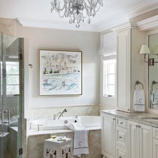 Пример оригинального дизайна: большая главная ванная комната в средиземноморском стиле с фасадами с выступающей филенкой, бежевыми фасадами, накладной ванной, угловым душем, бежевой плиткой, керамогранитной плиткой, бежевыми стенами, полом из керамогранита, врезной раковиной, столешницей из гранита, бежевым полом, душем с распашными дверями, серой столешницей, тумбой под две раковины и встроенной тумбой
