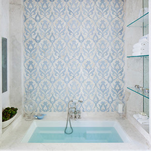 Photo of a large traditional ensuite bathroom in Los Angeles with raised-panel cabinets, white cabinets, beige tiles, stone slabs, white walls, ceramic flooring and a submerged bath.
