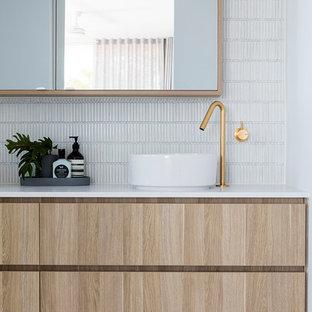 Inredning av ett modernt mellanstort vit vitt badrum, med släta luckor, skåp i ljust trä, vit kakel, mosaik, grå väggar, ett fristående handfat och grått golv