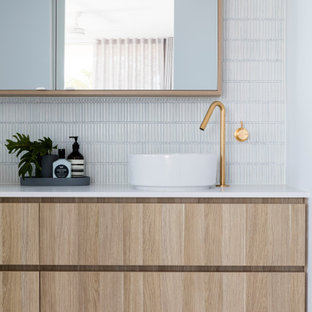 Photo of a beach style bathroom in Sunshine Coast with flat-panel cabinets, light wood cabinets, white tile, mosaic tile, white walls, pebble tile floors, a vessel sink, grey floor, white benchtops and a floating vanity.