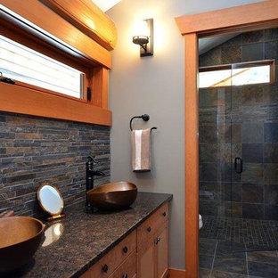 Foto de cuarto de baño con ducha, de estilo americano, grande, con lavabo sobreencimera, armarios con paneles empotrados, puertas de armario de madera clara, encimera de granito, ducha a ras de suelo, sanitario de una pieza, baldosas y/o azulejos de piedra y paredes beige