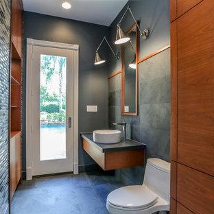Diseño de cuarto de baño con ducha, actual, pequeño, con armarios con paneles lisos, puertas de armario de madera oscura, sanitario de una pieza, lavabo sobreencimera, paredes grises, suelo de pizarra y suelo negro