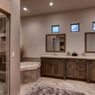 フェニックスの地中海スタイルのおしゃれな浴室 (落し込みパネル扉のキャビネット、オレンジのキャビネット、ドロップイン型浴槽、磁器タイル、磁器タイルの床、アンダーカウンター洗面器、珪岩の洗面台、開き戸のシャワー) の写真