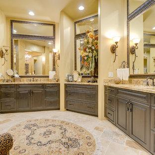 Immagine di una stanza da bagno padronale stile americano con ante con bugna sagomata, ante marroni, pavimento in travertino, lavabo sottopiano e top in granito
