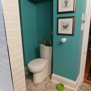Ejemplo de cuarto de baño con ducha, actual, de tamaño medio, con armarios con paneles lisos, puertas de armario de madera en tonos medios, bañera empotrada, combinación de ducha y bañera, sanitario de dos piezas, baldosas y/o azulejos grises, baldosas y/o azulejos de cemento, paredes azules, suelo de baldosas de porcelana, lavabo encastrado y encimera de madera