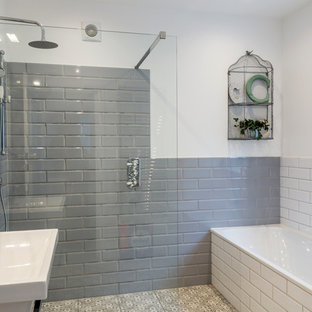 Inspiration for a medium sized traditional wet room in London with a corner bath, grey tiles, white tiles, metro tiles, white walls, multi-coloured floors and an open shower.