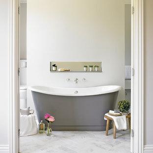 Modelo de cuarto de baño tradicional renovado con bañera exenta y paredes beige