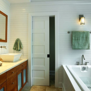 Example of a mid-sized beach style master travertine floor drop-in bathtub design in New York with shaker cabinets, medium tone wood cabinets, limestone countertops, a vessel sink and white walls