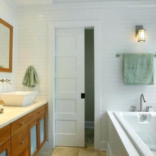 Exempel på ett mellanstort maritimt en-suite badrum, med luckor med glaspanel, skåp i mellenmörkt trä, bänkskiva i kalksten, beige kakel, stenhäll, ett platsbyggt badkar, en toalettstol med hel cisternkåpa, ett fristående handfat, vita väggar, travertin golv, en dubbeldusch och beiget golv