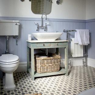 Mittelgroßes Shabby-Style Badezimmer mit verzierten Schränken, Schränken im Used-Look, Löwenfuß-Badewanne, Duschbadewanne, Wandtoilette mit Spülkasten, Zementfliesen, Mosaik-Bodenfliesen, bunten Wänden, Aufsatzwaschbecken und grauen Fliesen in Sussex