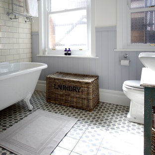 Photo of a medium sized rural bathroom in Sussex with a vessel sink, freestanding cabinets, distressed cabinets, wooden worktops, a claw-foot bath, a shower/bath combination, beige tiles and cement tiles.