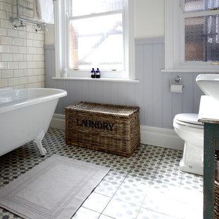 Esempio di una stanza da bagno country di medie dimensioni con lavabo a bacinella, consolle stile comò, ante con finitura invecchiata, top in legno, vasca con piedi a zampa di leone, vasca/doccia, piastrelle beige e piastrelle di cemento