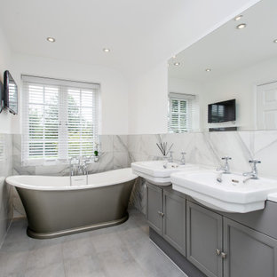 Design ideas for a medium sized traditional ensuite bathroom in Surrey with shaker cabinets, grey cabinets, a freestanding bath, grey tiles, white walls, ceramic flooring, a built-in sink, quartz worktops, grey floors, white worktops and double sinks.