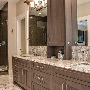 Стильный дизайн: большая главная ванная комната в классическом стиле с фасадами с утопленной филенкой, коричневыми фасадами, отдельно стоящей ванной, душевой комнатой, унитазом-моноблоком, разноцветной плиткой, плиткой из листового камня, бежевыми стенами, полом из керамической плитки, врезной раковиной, столешницей из искусственного кварца, серым полом и душем с распашными дверями - последний тренд