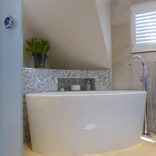 Design ideas for a small contemporary ensuite bathroom in Hampshire with glass-front cabinets, brown cabinets, a freestanding bath, a walk-in shower, a wall mounted toilet, beige tiles, stone tiles, limestone flooring, a console sink and glass worktops.