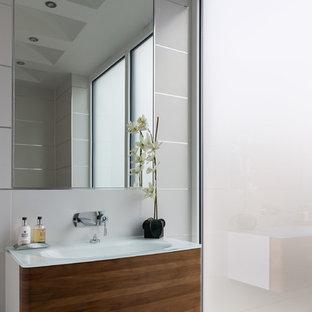 Immagine di una grande stanza da bagno con doccia minimalista con consolle stile comò, ante in legno bruno, piastrelle bianche, pareti bianche, pavimento in gres porcellanato, lavabo a consolle, top in legno e pavimento nero