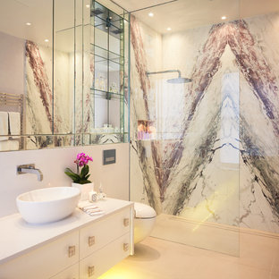 This is an example of a contemporary shower room in London with flat-panel cabinets, white cabinets, a built-in shower, a wall mounted toilet, white walls, a vessel sink and an open shower.
