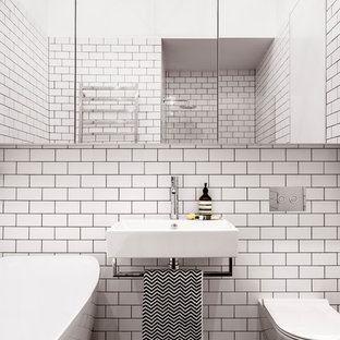 This is an example of a small contemporary bathroom in Sydney with a freestanding bath, an alcove shower, a wall mounted toilet, white tiles, metro tiles, white walls, mosaic tile flooring, a wall-mounted sink, glass-front cabinets, copper worktops, black floors and a hinged door.