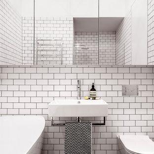 На фото: с высоким бюджетом маленькие ванные комнаты в современном стиле с отдельно стоящей ванной, душем в нише, инсталляцией, белой плиткой, плиткой кабанчик, белыми стенами, полом из мозаичной плитки, подвесной раковиной, стеклянными фасадами, столешницей из меди, черным полом и душем с распашными дверями