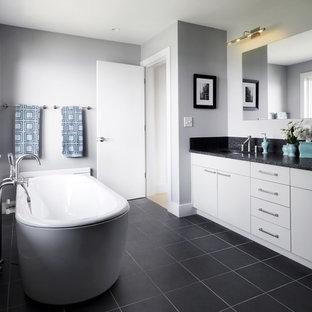 Example of a trendy black floor freestanding bathtub design in Burlington with black countertops