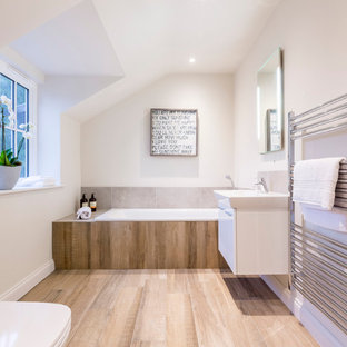 Photo of a contemporary bathroom in London with flat-panel cabinets, white cabinets, an alcove bath, brown tiles, white walls, a console sink and a two-piece toilet.