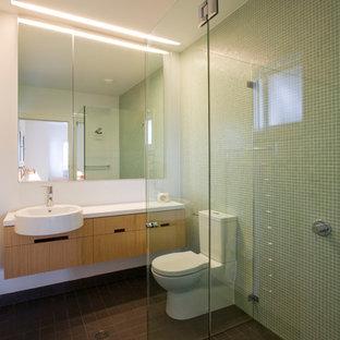 Пример оригинального дизайна: детская ванная комната среднего размера в стиле модернизм с плоскими фасадами, светлыми деревянными фасадами, столешницей из ламината, настольной раковиной, унитазом-моноблоком, зеленой плиткой, плиткой мозаикой и белыми стенами