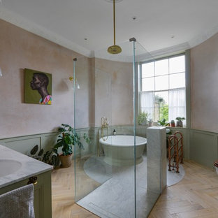 Example of a large eclectic master bathroom design in London with green cabinets, a wall-mount toilet, a drop-in sink and marble countertops