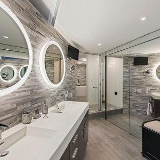 Großes Modernes Badezimmer En Suite mit flächenbündigen Schrankfronten, dunklen Holzschränken, beigefarbenen Fliesen, Mosaikfliesen, Terrakottaboden, Einbauwaschbecken, Laminat-Waschtisch und grauer Wandfarbe in New York