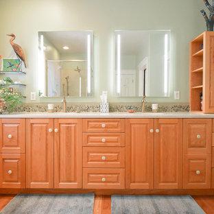 ポートランドの大きいトラディショナルスタイルのおしゃれなマスターバスルーム (フラットパネル扉のキャビネット、中間色木目調キャビネット、コーナー設置型シャワー、一体型トイレ、緑の壁、無垢フローリング、アンダーカウンター洗面器、珪岩の洗面台、開き戸のシャワー、白い洗面カウンター) の写真