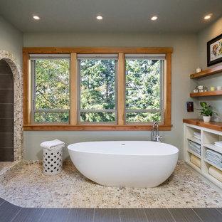 Ejemplo de cuarto de baño principal, rural, con puertas de armario blancas, bañera exenta, ducha abierta, encimera de madera, paredes grises, suelo de baldosas tipo guijarro y ducha abierta