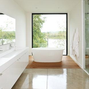 Diseño de cuarto de baño principal, moderno, de tamaño medio, con lavabo de seno grande, armarios con paneles lisos, puertas de armario blancas, bañera exenta, ducha empotrada, baldosas y/o azulejos blancos, suelo de cemento y paredes blancas