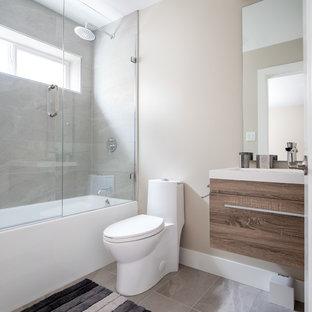 Cette image montre une petit salle d'eau design avec un WC à poser, sol en stratifié, un plan vasque, un plan de toilette en verre, un sol marron, un plan de toilette bleu, un placard à porte plane, des portes de placard marrons, une baignoire encastrée, un combiné douche/baignoire, un carrelage gris, des carreaux de porcelaine, un mur beige et une cabine de douche à porte battante.