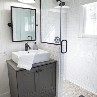 Пример оригинального дизайна: маленькая ванная комната в стиле кантри с настольной раковиной, фасадами в стиле шейкер, искусственно-состаренными фасадами, угловым душем, белыми стенами, душевой кабиной, галечной плиткой, полом из керамогранита, столешницей из дерева и белой плиткой