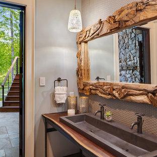 Imagen de cuarto de baño rural con baldosas y/o azulejos grises, baldosas y/o azulejos en mosaico, paredes grises, lavabo de seno grande, encimera de madera y encimeras marrones